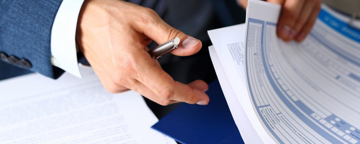 Man Doing Paperwork To Arrange Insurance Premium Funding